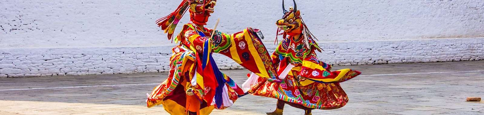 See masked dancers at a Tshechu (Bhutanese festival) a on a tailor-made holiday to Bhutan