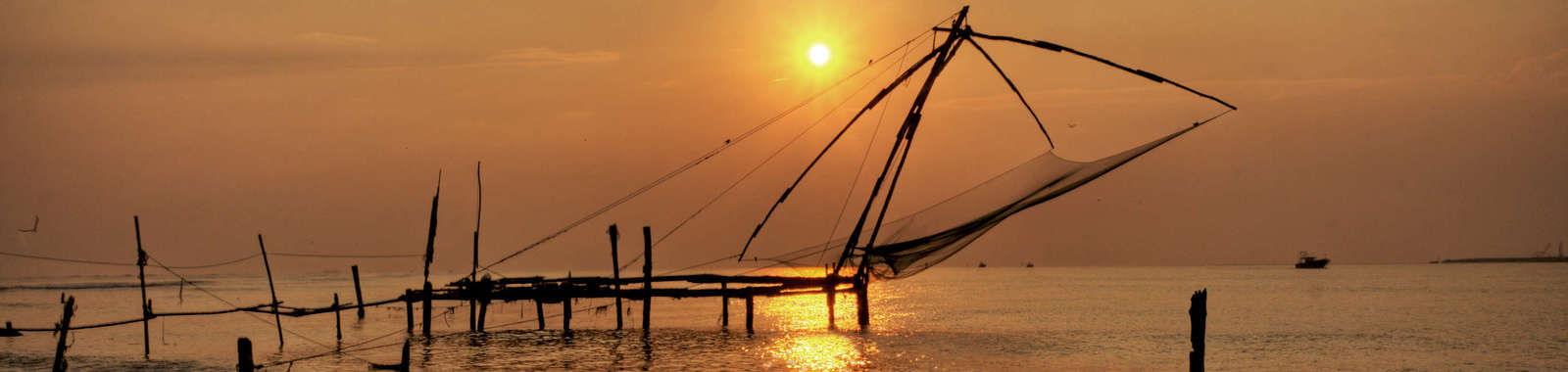Experience a magical sunset at Cochin's famous fishing nets on a luxury holiday to Kerala